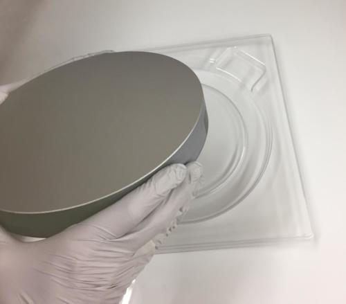 Medium sized optic being placed into a tray for storage